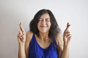 woman with fingers crossed as if she is wishing