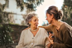 elderly woman hugging daughter discussing investment accounts