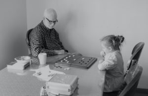 grandpa playing a game with granddaughter thinking about beneficiaries
