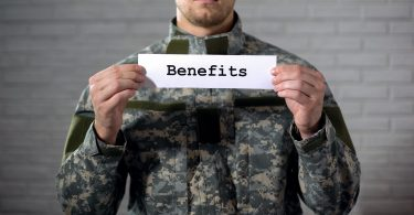Benefits word written on sign in hands of male soldier, veterans support, aid